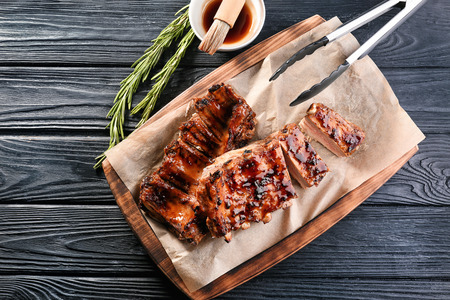 Board with delicious pork ribs on wooden table