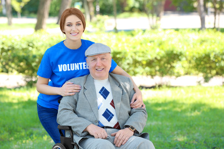 Happy senior man on wheelchair with young female volunteer outdoors
