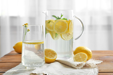 Jug and glass with refreshing lemon water on wooden table