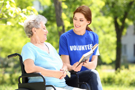 Young female volunteer reading book to senior woman on wheelchair outdoors