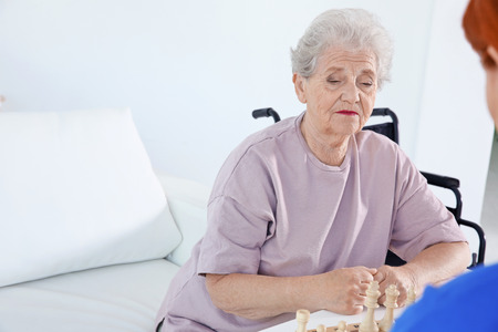 Young female volunteer playing chess with elderly woman in light room Stock Photo