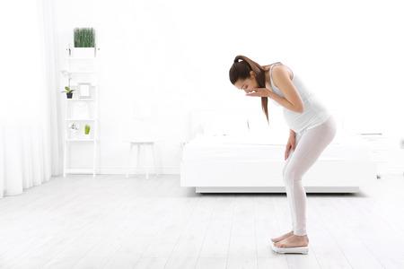 Zwangere vrouw die zich thuis op schalen bevindt. Zwangerschap gewichtstoename concept