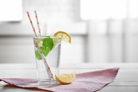 Refreshing lemon water in glass with straw on cute napkin