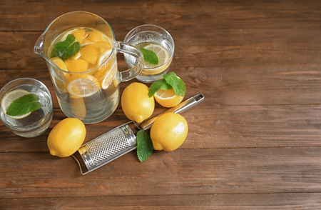 Jug and glasses with refreshing lemon water on wooden table