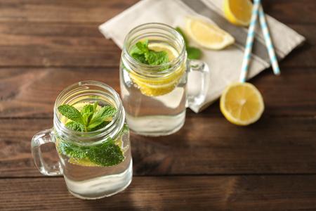 Refreshing lemon water in glass mason jars on wooden table Stok Fotoğraf
