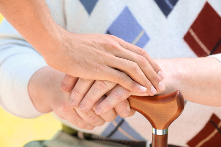 Hand of young volunteer supporting senior man with cane, closeup