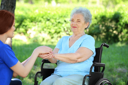 Happy senior woman on wheelchair with young female volunteer outdoors Stock Photo