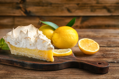 Piece of yummy lemon meringue pie on wooden table 免版税图像 - 110132387