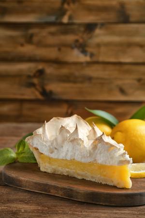 Pezzo di deliziosa torta di meringa al limone su un tavolo di legno Archivio Fotografico
