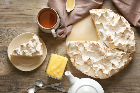 Yummy lemon meringue pie with tea on wooden table Foto de archivo