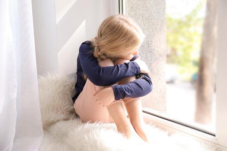 Cute sad girl sitting on window sill at home Stock Photo