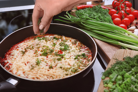 Woman pouring dill on eggs in purgatory