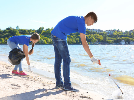 Young people cleaning beach area. Volunteer concept