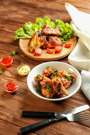Tasty chicken and small bowls with sauces on wooden table Foto de archivo