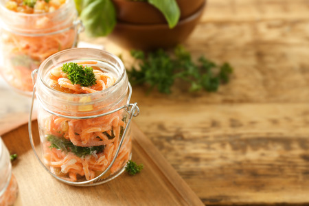Jar with delicious carrot raisin salad on wooden background 版權商用圖片