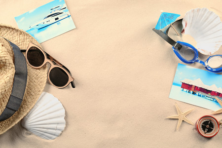 Composition with beach accessories and pictures on sand. Concept of travel and vacation