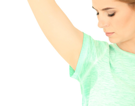 Young woman with sweat stain on her t-shirt against white background. Concept of using deodorant