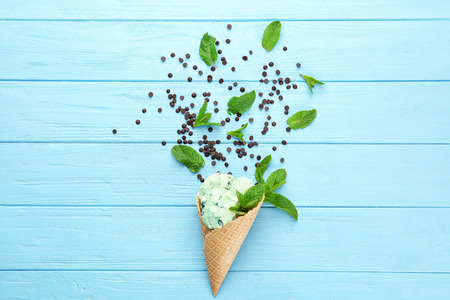 Composition of delicious mint chocolate chip ice cream in waffle cone and fresh leaves on wooden background