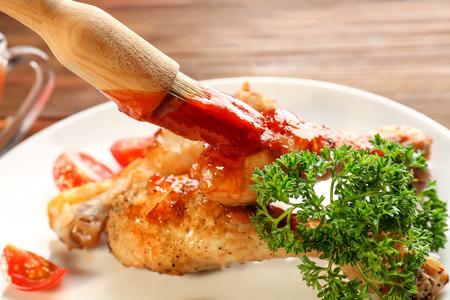Spreading tasty tomato sauce on chicken legs