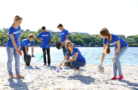 Group of young people cleaning beach area. Volunteer concept Banco de Imagens