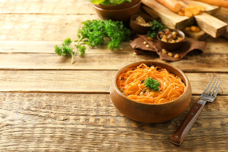 Bowl with delicious carrot raisin salad on wooden table