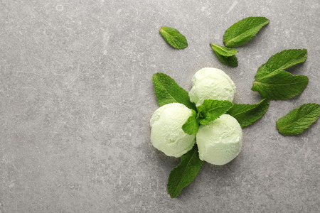 Balls of delicious mint chocolate chip ice cream and fresh leaves on grey table