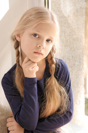 Cute little girl near window at home