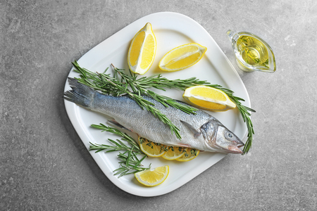 Fresh fish stuffed with rosemary and slices of lemon on table