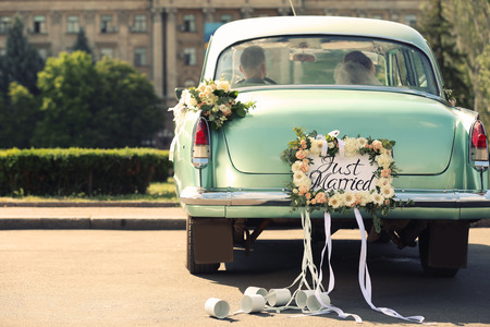 Wedding couple in car decorated with plate JUST MARRIED and cans outdoors 免版税图像