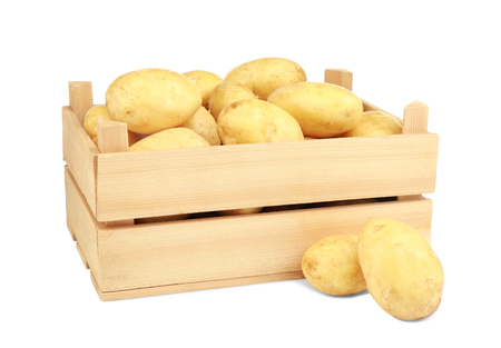 Wooden box with potatoes on white background