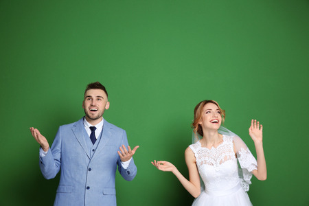 Happy wedding couple on color background 免版税图像