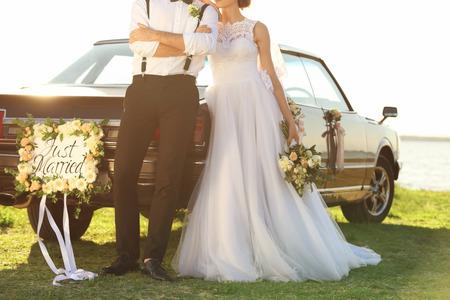Glückliches Hochzeitspaar in der Nähe von dekoriertem Auto am Ufer Standard-Bild