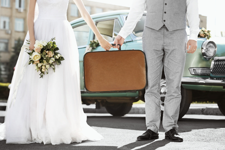 Happy wedding couple with suitcase and car outdoors Imagens