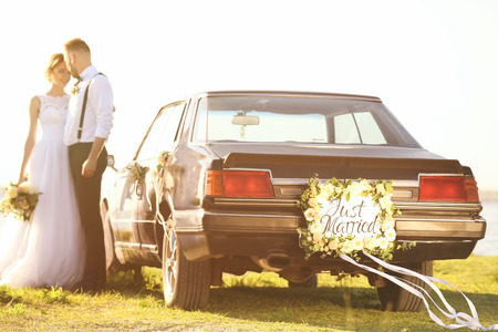 Happy wedding couple near decorated car outdoors Imagens
