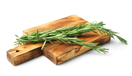 Wooden board with fresh rosemary on white background