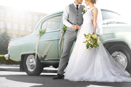 Happy wedding couple near decorated car outdoors Фото со стока