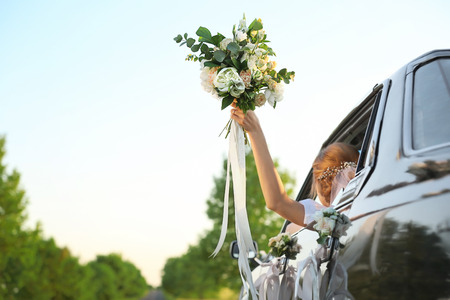 Beautiful young bride holding bouquet in decorated car Standard-Bild