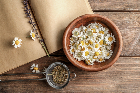 Flowers in bowl, strainer with dried chamomile and blank book on wooden background