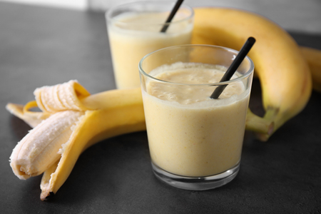 Delicious banana homemade smoothie in glass on grey background