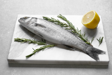 Fresh fish with rosemary and lemon on gray background