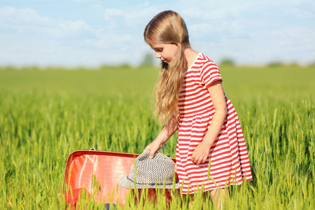 Little girl with suitcase in green field