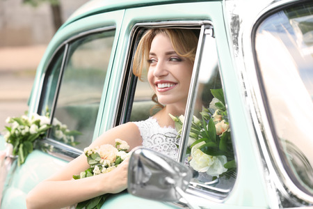 Beautiful young bride in decorated car