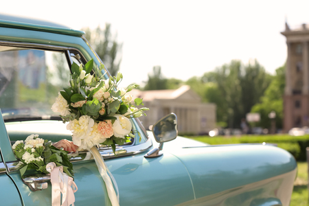 Beautiful young bride holding bouquet in decorated car, outdoors