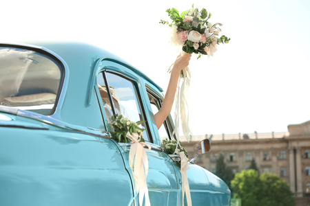 Beautiful young bride holding bouquet in decorated car outdoors
