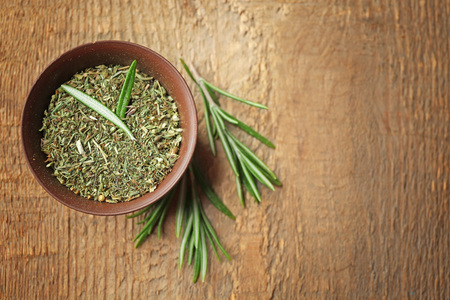 Bowl with dried herbs and fresh rosemary on table Imagens