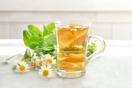 Herbal tea with lemon in glass cup and chamomile flowers on table
