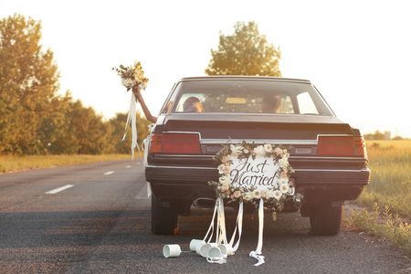 Happy wedding couple in decorated car