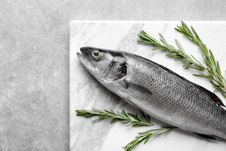 Fresh fish with rosemary on gray background Imagens