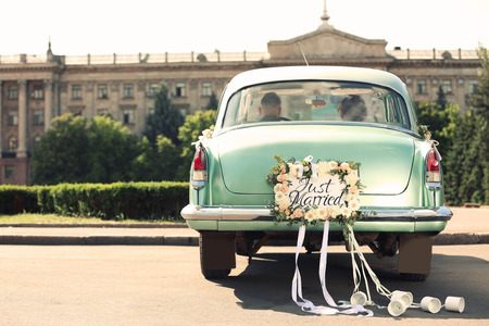 Wedding couple in car decorated with plate JUST MARRIED and cans outdoors 스톡 콘텐츠