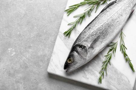 Fresh fish with rosemary on gray background Reklamní fotografie
